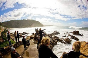 Spectators  watching massive 6-7 metre waves at Victoria Bay, while 3 brave surfers contemplate a daring paddle out