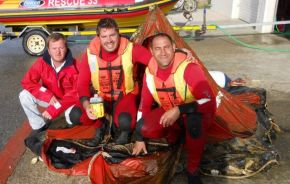 Quentin Denier, Attie Gunter and Leon Pretorius with the life raft that they found today from the yacht Gulliver.