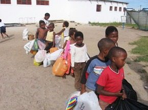 Children carrying big bags of recylable items to a weighing table.