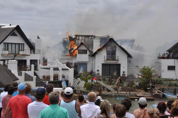 Crowd watches the cnal house burning at lunch time today. Photo: Sharon Welman